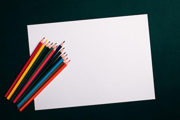 Vue de dessus feuille blanche et crayons de couleur sur fond noir