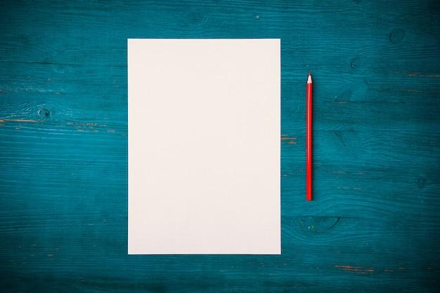 Vue de dessus d'une feuille blanche vierge et d'un crayon sur fond de bois bleu texturé