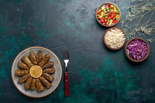 Vue de dessus feuille dolma repas de viande de l'est roulé à l'intérieur des feuilles vertes avec des légumes tranchés sur le plat de dîner de viande de bureau bleu est repas