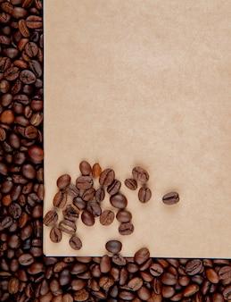 Vue de dessus de la feuille de papier kraft brun sur fond de grains de café