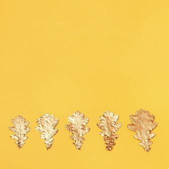 Vue de dessus des feuilles de chêne peintes d'or sur fond jaune. carte de voeux automnale. vue d'en-haut.