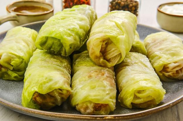 Vue de dessus des feuilles de chou roulées farcies de viande hachée, de riz et d'oignons sur une table en bois blanc