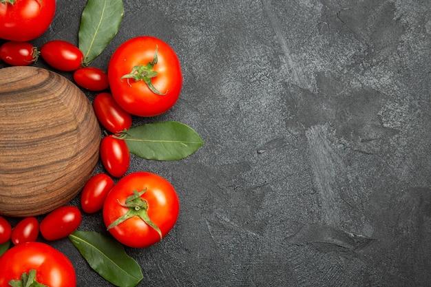 Vue de dessus les feuilles de laurier cerise et tomates rouges autour d'une plaque en bois sur la gauche du sol sombre avec copie spase