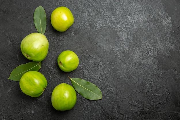 Vue de dessus les feuilles de laurier de tomates vertes sur la gauche de la surface sombre