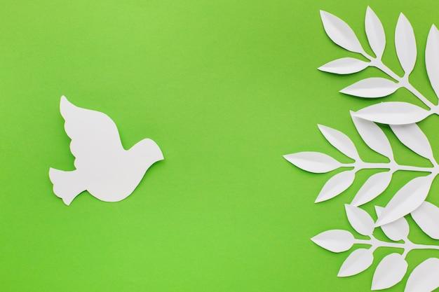 Vue de dessus des feuilles de papier et de la colombe pour la journée de la paix
