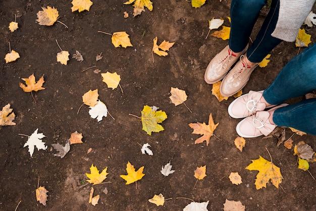 Vue de dessus des feuilles sur le sol et les pieds de deux filles