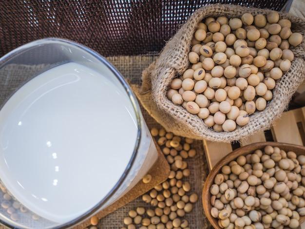 Vue de dessus. fèves de soja et verre de lait de soja. placé sur une table avec des sacs.