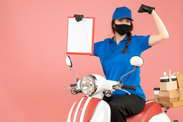 Vue de dessus d'une fière coursière portant un masque médical et des gants assis sur un scooter tenant une feuille de papier vide livrant des commandes sur fond de pêche pastel