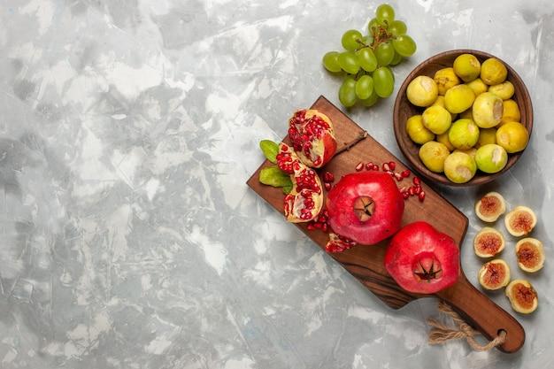 Vue de dessus des figues fraîches aux grenades et raisins sur un bureau blanc