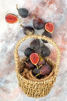Vue de dessus des figues fraîches éparpillées du panier sur fond nu