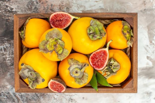 Vue de dessus des figues de kakis frais dans une boîte en bois sur fond nude