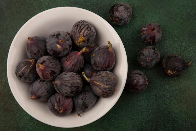 Vue de dessus des figues de mission douce violet foncé sur un bol sur une surface verte