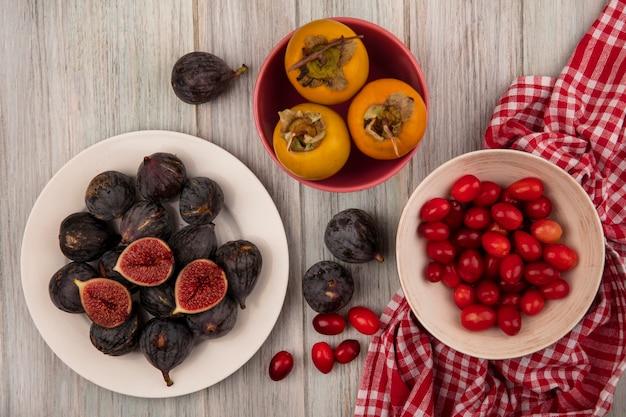 Vue de dessus des figues de mission noires mûres sur un bol blanc avec des cerises de cornaline sur un bol sur un tissu vérifié avec des fruits kaki sur un mur en bois gris