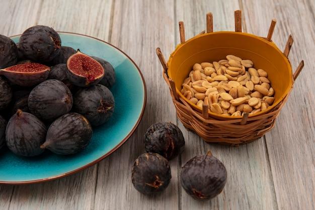 Vue de dessus des figues de mission noires mûres sur un bol bleu avec des arachides sur un seau sur un mur en bois gris