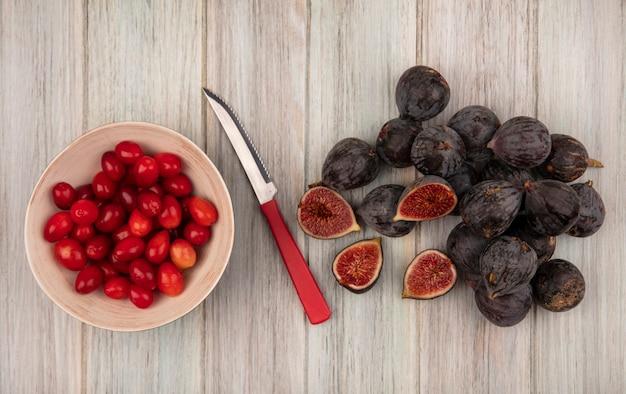 Vue de dessus des figues de mission noires mûres fraîches avec des cerises de cornaline sur un bol avec un couteau sur un mur en bois gris
