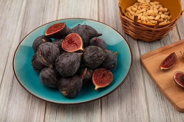 Vue de dessus des figues de mission violet foncé sur un bol bleu avec des tranches de figues noires sur une planche de cuisine en bois sur une surface en bois gris