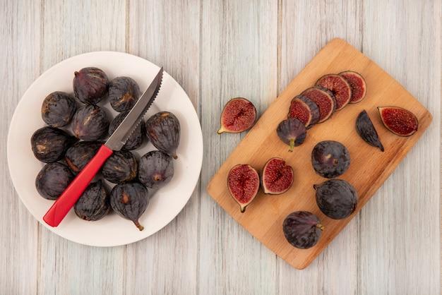 Vue de dessus des figues noires fraîches sur un bol blanc avec un couteau avec des figues coupées en deux sur une planche de cuisine en bois sur un mur en bois gris