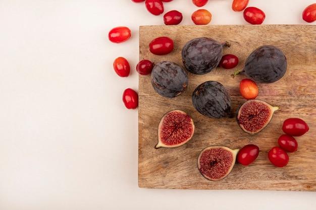 Vue de dessus des figues noires fraîches sur une planche de cuisine en bois avec des cerises cornaline isolé sur un mur blanc avec copie espace