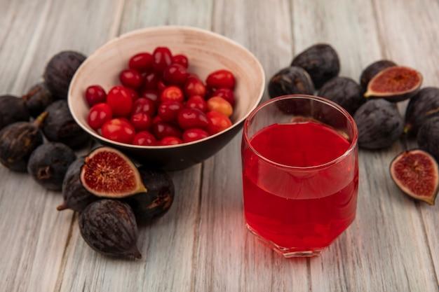 Vue de dessus des figues noires de mission avec des cerises de cornaline sur un bol avec du jus de fruits frais sur un verre sur un mur en bois gris