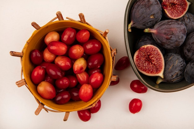 Vue de dessus des figues noires mûres fraîches sur un bol avec des cerises de cornaline sur un seau sur un mur blanc