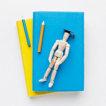Vue de dessus de la figurine en bois sur des livres avec des crayons