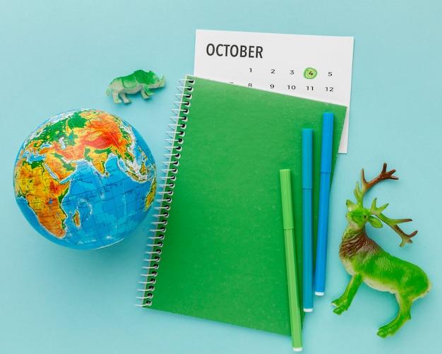 Vue de dessus de la figurine de cerf avec la planète terre et cahier pour la journée des animaux