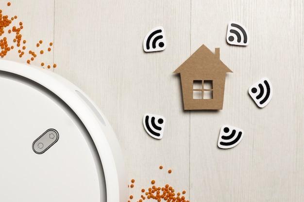 Vue de dessus de la figurine de maison avec aspirateur contrôlé par wi-fi