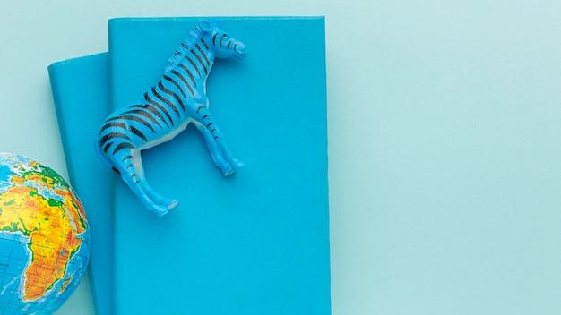 Vue de dessus de la figurine de zèbre avec la planète terre et des livres pour la journée des animaux