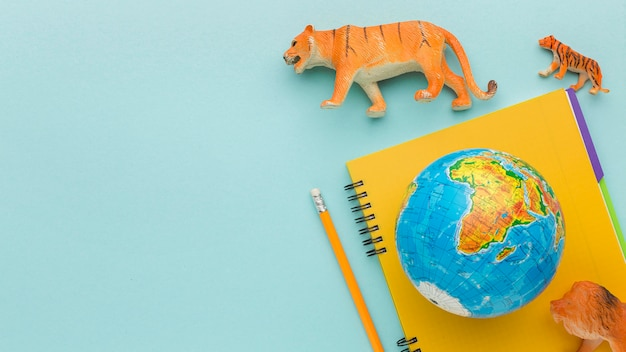 Vue de dessus des figurines animales avec cahier et planète terre pour la journée des animaux