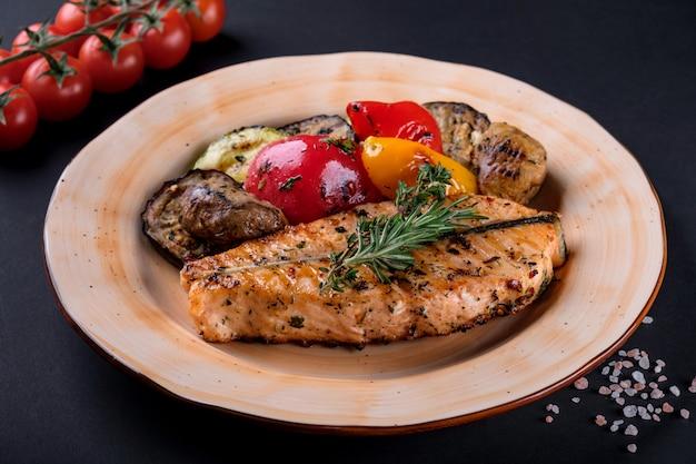 Vue de dessus de filet de saumon steak grillé avec salade de légumes, poivre, herbes sur la plaque