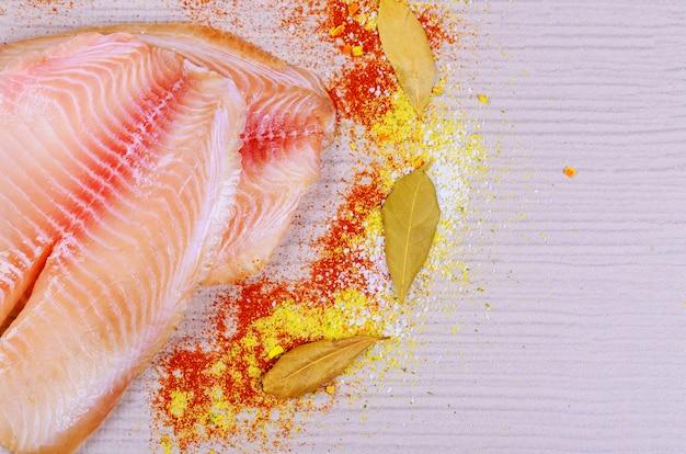 Vue de dessus de filets de tilapia frais crus sur une planche à découper