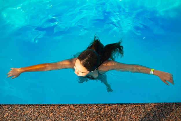 Vue de dessus fille adolescente nage dans la piscine