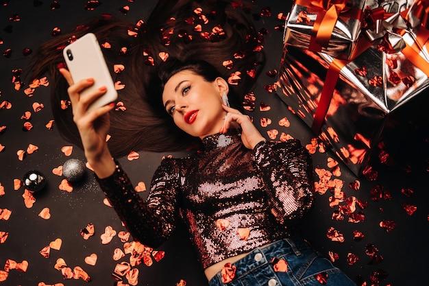 Vue de dessus d'une fille couchée dans des vêtements brillants sur le sol en confettis en forme de coeurs et prenant un selfie.