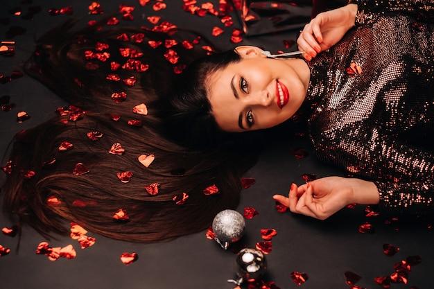 Vue de dessus d'une fille couchée dans des vêtements brillants sur le sol en confettis en forme de coeurs.