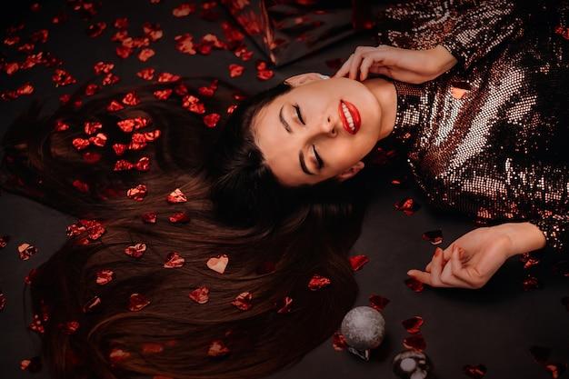 Vue de dessus d'une fille couchée dans des vêtements brillants sur le sol en confettis en forme de coeurs