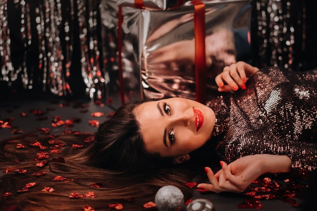 Vue de dessus d'une fille couchée dans des vêtements brillants sur le sol en confettis sous forme de coeurs et de cadeaux.