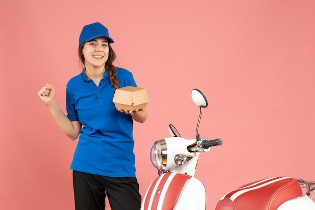 Vue de dessus d'une fille de courrier heureuse debout à côté d'une moto tenant un gâteau sur fond de couleur pêche pastel