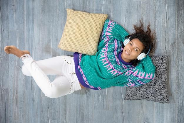 Vue de dessus d'une fille latine souriante et détendue, écoutant de la musique gisant sur le sol de sa maison. espace pour le texte.