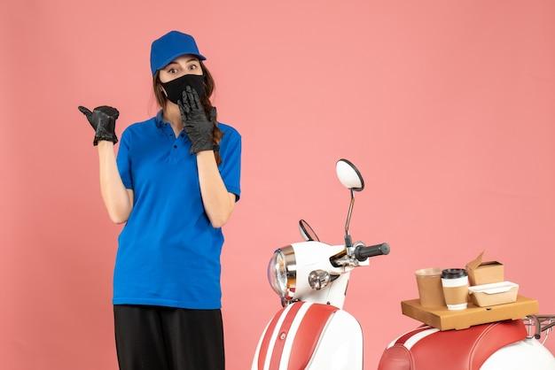 Vue de dessus d'une fille de messagerie confuse dans un masque médical debout à côté d'une moto avec un gâteau au café dessus sur fond de couleur pêche pastel
