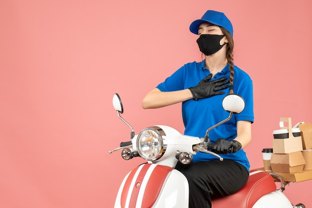 Vue de dessus d'une fille de messagerie pleine d'espoir portant un masque médical et des gants assis sur un scooter livrant des commandes sur fond de pêche pastel