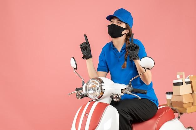 Vue de dessus d'une fille de messagerie portant un masque médical et des gants assis sur un scooter livrant des commandes pointant vers le haut sur fond de pêche pastel