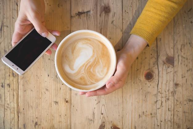 Vue de dessus d'une fille travaillant au téléphone et buvant du café assis à une table en bois
