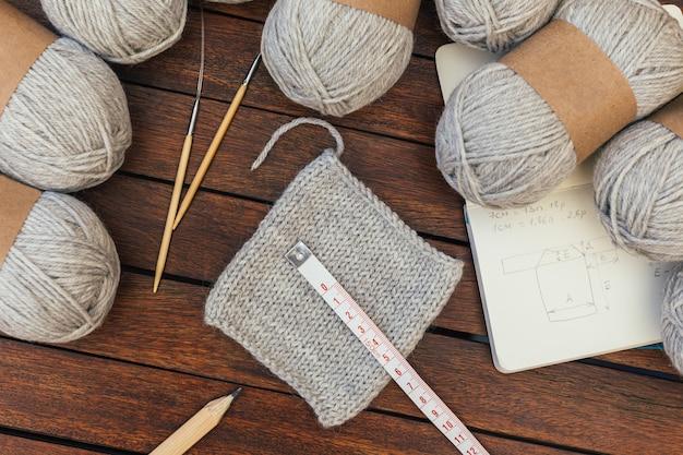 Vue de dessus des fils à tricoter gris, aiguilles sur fond en bois marron avec schéma de pull. tester une laine avec une pièce tricotée