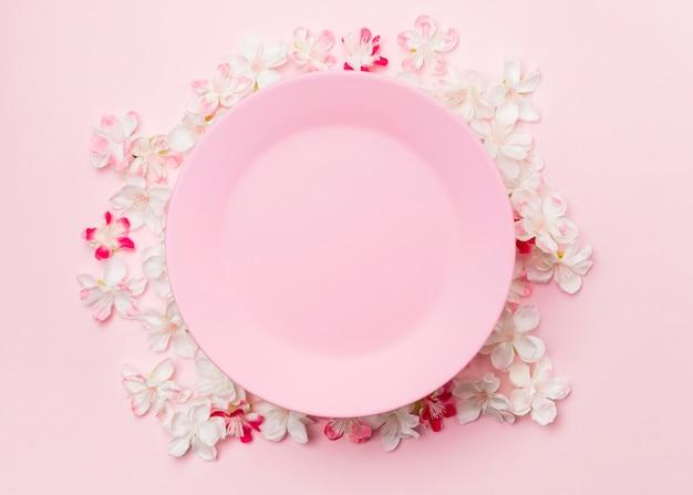 Vue de dessus fleurs et assiette rose