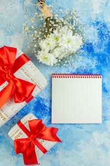 Vue de dessus fleurs blanches cadeaux bloc-notes de différentes tailles sur fond bleu