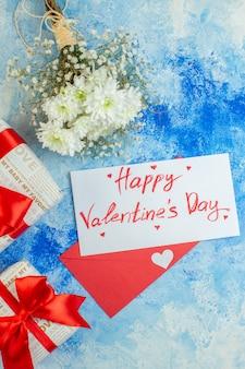Vue de dessus fleurs blanches cadeaux joyeux saint valentin écrit sur une enveloppe de lettre rouge sur fond bleu
