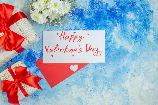 Vue de dessus fleurs blanches cadeaux de vacances joyeux saint valentin écrit sur lettre enveloppe rouge sur fond bleu