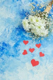Vue de dessus fleurs blanches petits coeurs rouges sur fond bleu