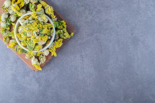 Vue de dessus des fleurs de camomille séchées sur planche de bois.
