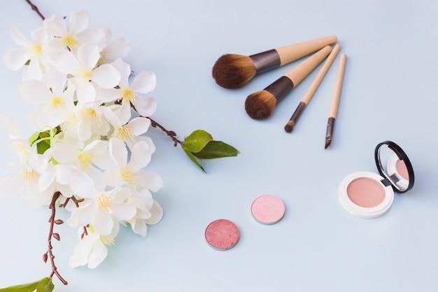 Une vue de dessus de fleurs de cerisier; pinceau de maquillage; fard à joues sur fond coloré
